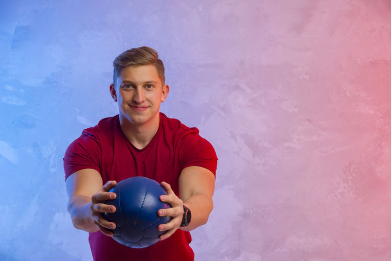 Portrait of smiling young man holding exercise ball against wall