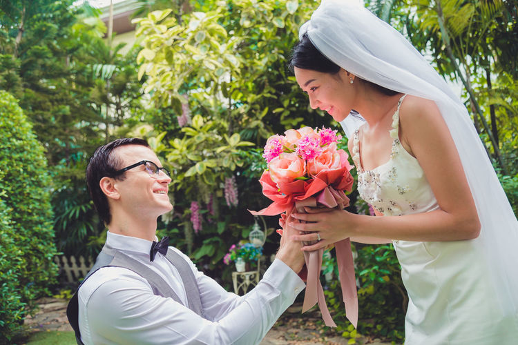Side view of couple holding bouquet against plants