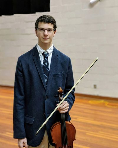 Portrait of young man holding violin while standing on hardwood floor