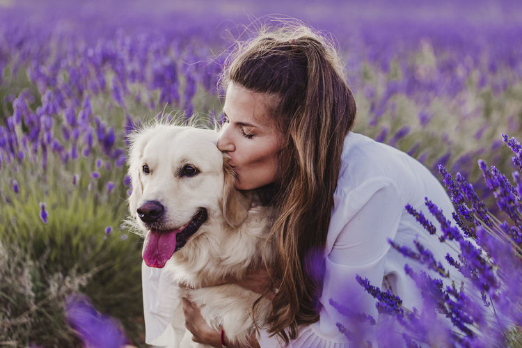 Woman kissing dog by purple flowering plants on land