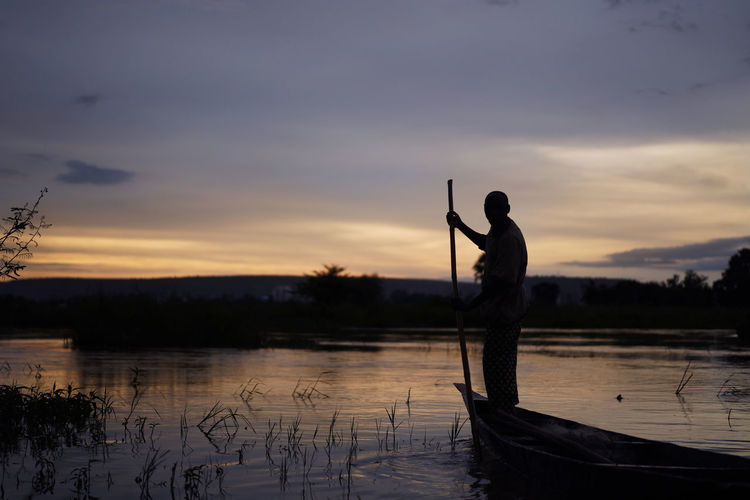 Man standing on boat amidst lake against sky during sunset
