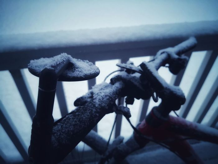 Close-up of bicycle on railing during winter
