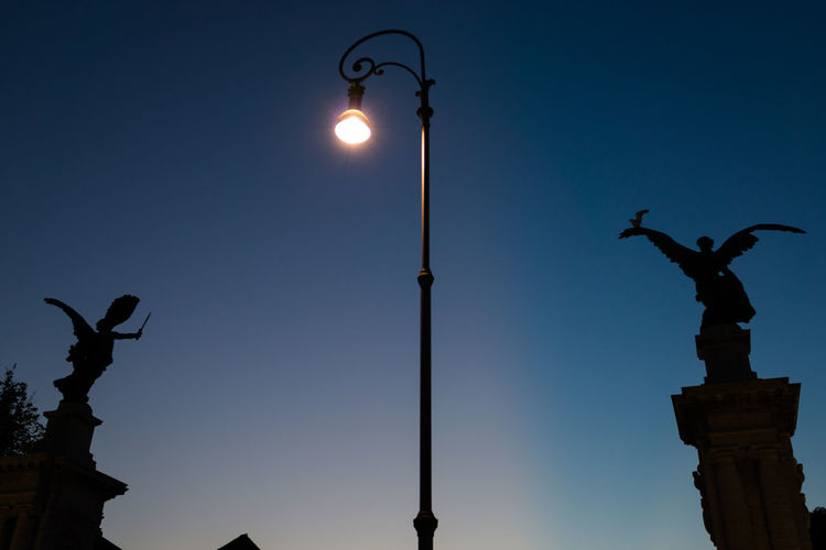 Low angle view of statue against illuminated street light