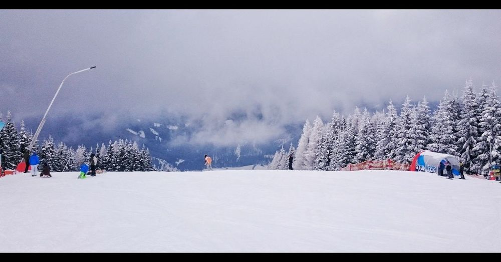 Panoramic view of people on snow covered landscape