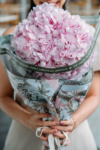 Midsection of woman holding pink flower