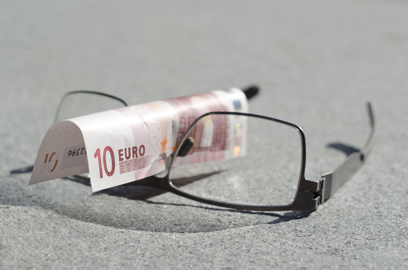 Close-Up Of Eyeglasses With Paper Currency On Table