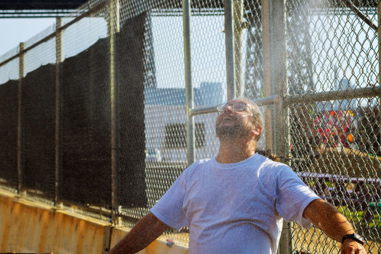 Man looking up while standing against chainlink fence