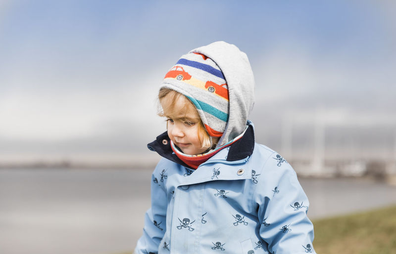 Toddler girl standing on dyke and looking down – Hindeloopen, Netherlands, Europe Coastline Exploring Happy Innocence Looking Down Netherlands Winter Caucasian Child Childhood Cute Friesland Front View Girl Head And Shoulders Headshot Ijsselmeer Knit Hat One Person Outdoors Portrait Toddler  Waist Up Warm Clothing Water
