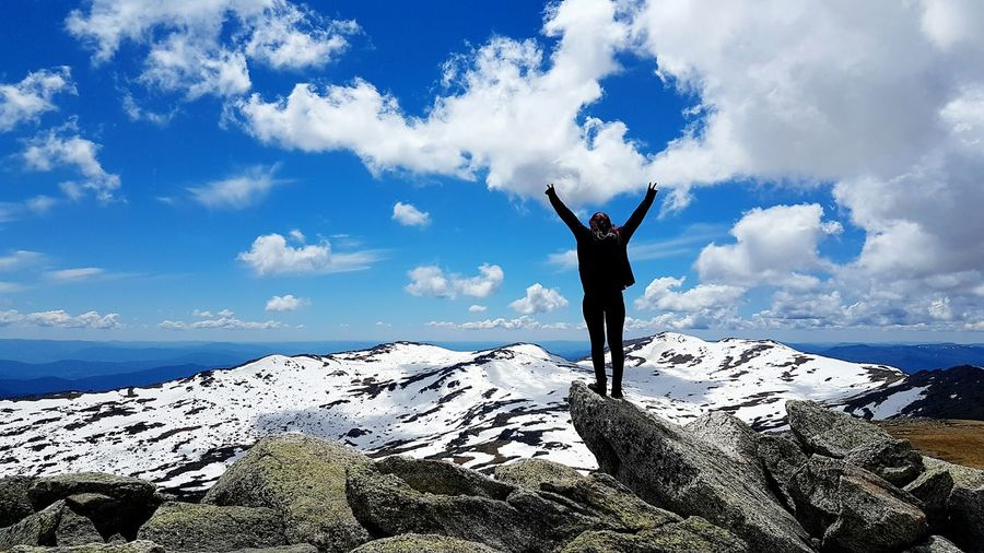 Rear view of woman standing on cliff against snowcapped mountains