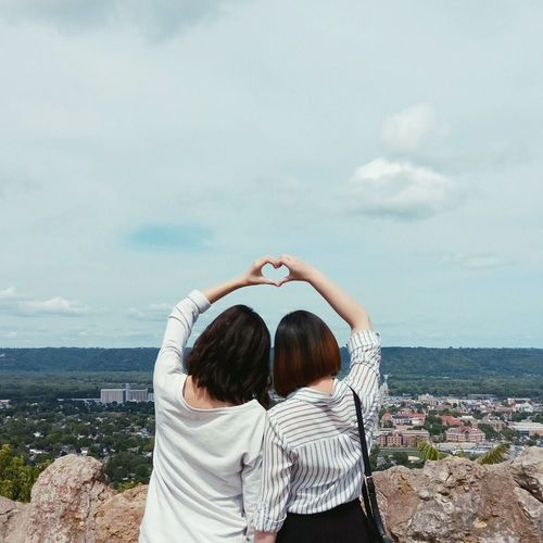 Rear View Of Friends Making Heart Shape Against Sky