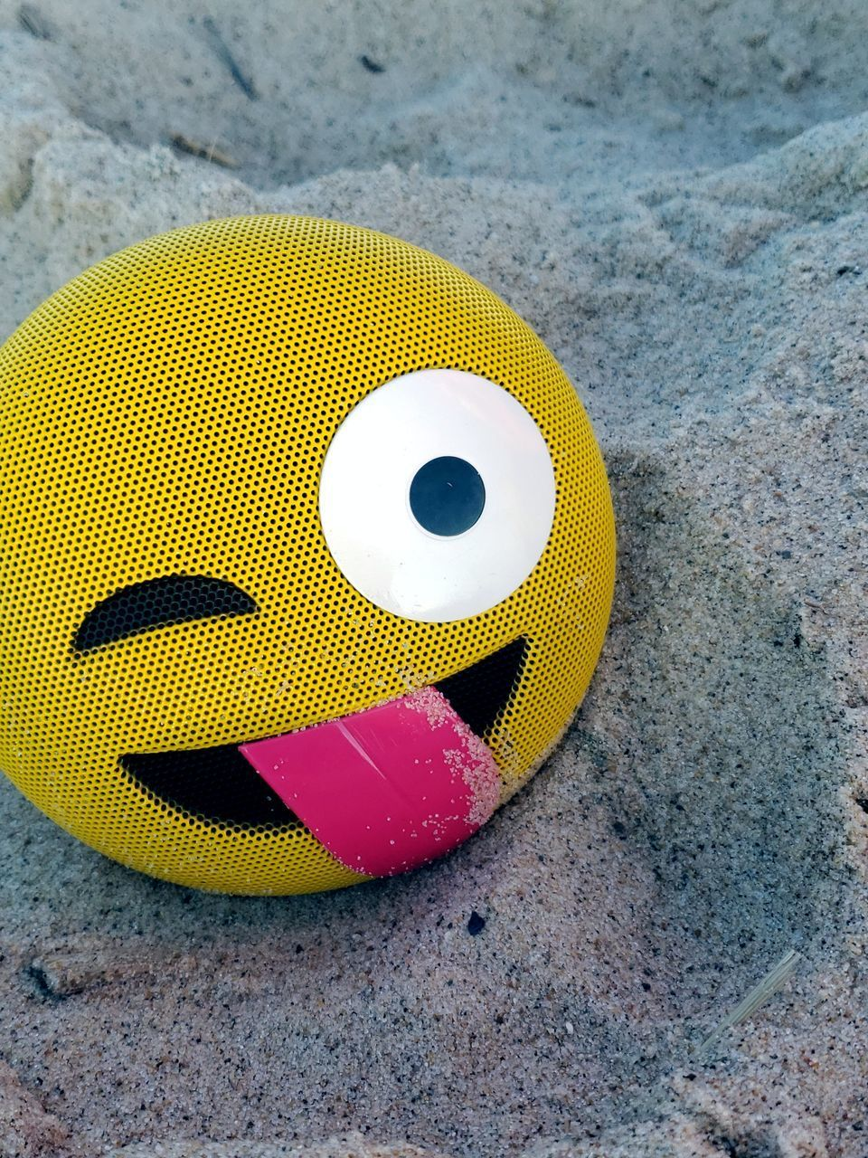 yellow, no people, sand, land, high angle view, beach, close-up, still life, sport, day, ball, nature, art and craft, outdoors, single object, sports equipment, smiling, representation, focus on foreground, anthropomorphic smiley face, personal accessory