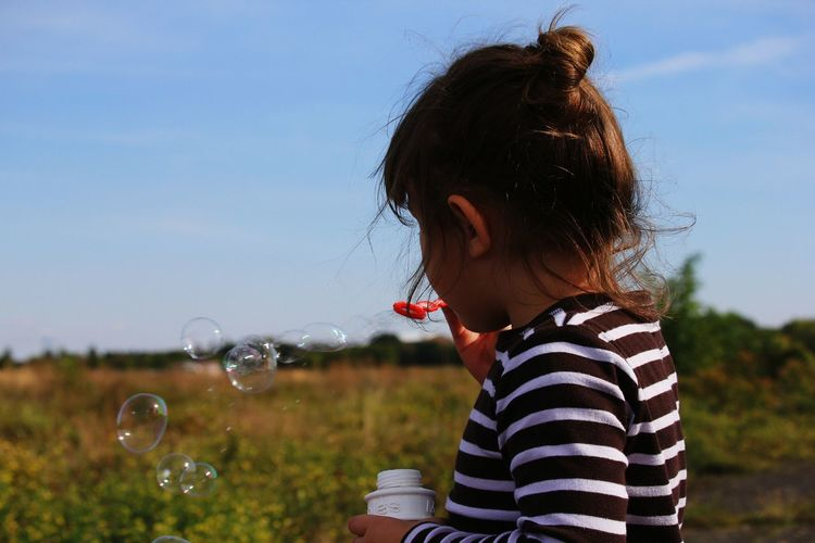 Close-up of girl blowing bubbles on field against sky