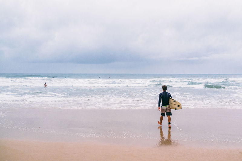 Beach Beauty In Nature Brazil Cloud Cloud - Sky Day Florianópolis Leisure Activity Lifestyles Man Nature Outdoors Rear View Sand Scenics Sea Sky Standing Surf Surfer Surfing Vacations Walking Water Wave