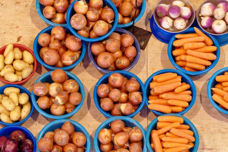 Directly Above Shot Of Root Vegetables In Plastic Containers At Market Stall