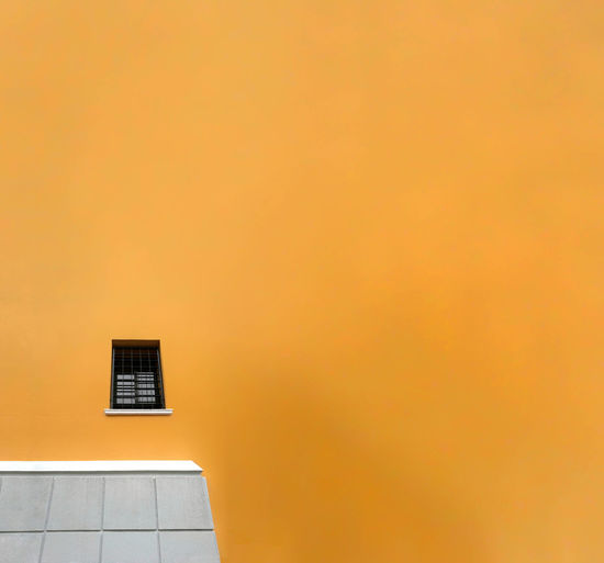 Low Angle View Of Window On Orange Wall