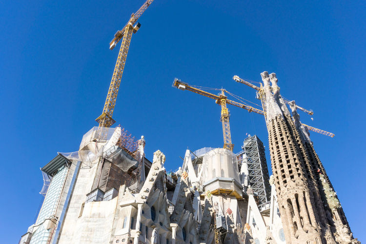 Low angle view of sagrada familia against clear blue sky in city