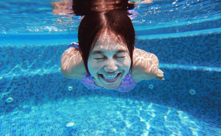 Underwater shot of young woman diving into the swimming pool. Woman ASIA Underwater Pool Water Diving Swimming Swim Happy Smile Beautiful Female Thailand Thai Lady Girl Exercise Action Activity Attractive Bikini Blue Body Part Fun Happiness Healthy Joy Leisure Lifestyles People person Sports Summer Under Active Dive Portrait Wet Young Swimming Pool One Person Leisure Activity Nature Women Eyes Closed  Headshot