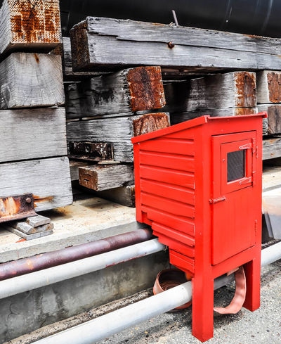 Bright red fire hose reel box with shipping port wood dunnage in the background in Fremantle, Western Australia. Beams Box Cabinet Cribbage Day Dock Dunnage Equipment Fire Department Fire Hose Firehose Freight Hose Industry No People Portrait Precaution Prevention Red Reel Safety Shipping  Tranportation Vibrant Color Wood