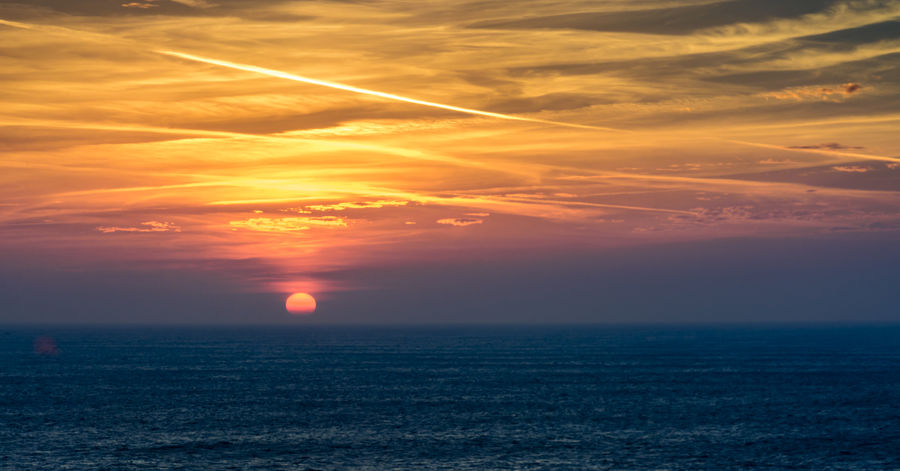 Sunset at Lands End, Cornwall, UK in late Autumn Beauty In Nature Dramatic Sky Horizon Over Water Idyllic LandsEnd Nature No People Orange Sky Outdoors Scenics Sea Sea And Sky Seascape Sky Sun Sunset Sunset_collection Tranquil Scene Tranquility Vapourtrail Water