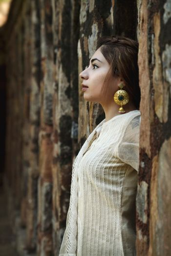 Side view of woman standing by wooden wall