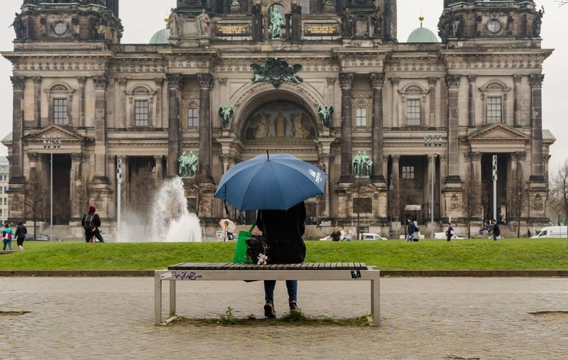 Rear view of woman sitting with umbrella on bench at berlin cathedral