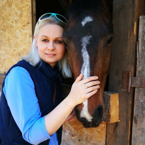 Portrait Of Woman Petting Horse In Stable