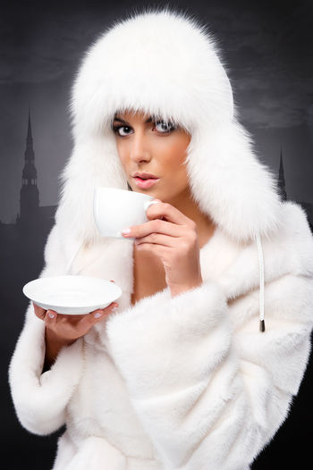 Portrait Of Young Woman In Fur Coat Holding Cup And Saucer Against Wall