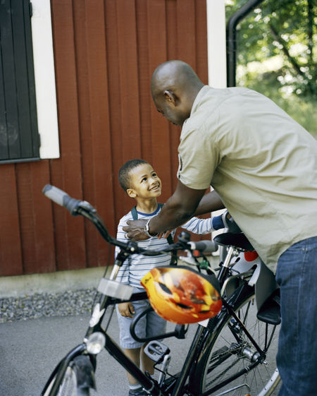 Full length of father with child on bicycle