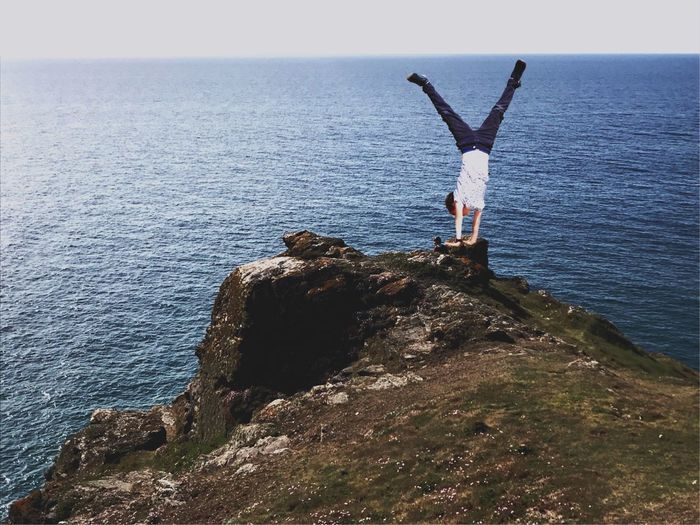 Boy Doing Handstand On Cliff By Sea