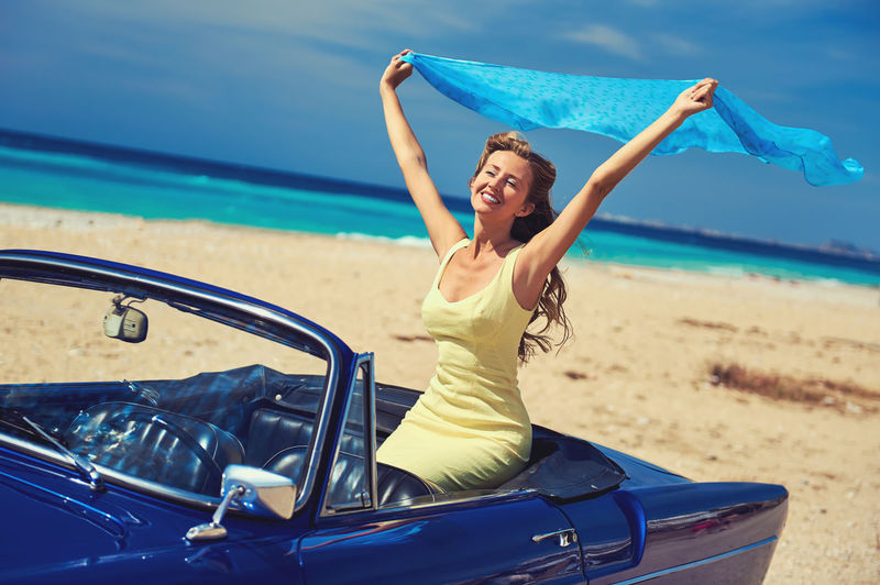 Smiling woman holding aloft scarf while sitting in car by sea against sky