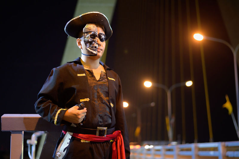 Young man wearing pirate costume standing against sky at night