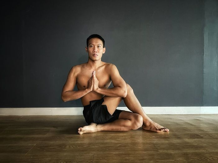 Portrait of shirtless young man sitting on floor against wall