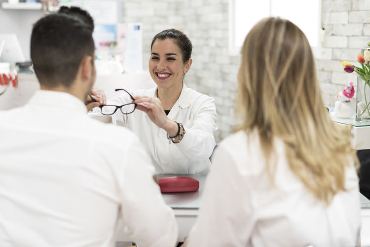 Optometrist assisting patient in trying eyeglasses at store