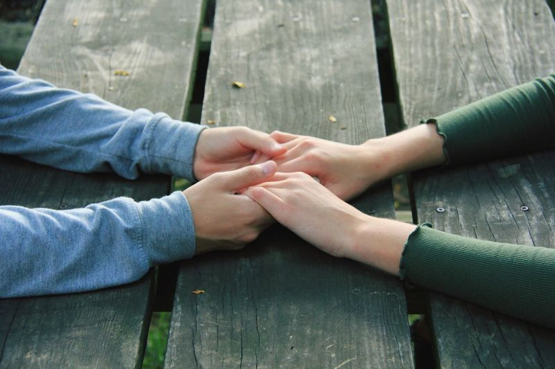 Cropped Image Of Couple Holding Hands At Wooden Table