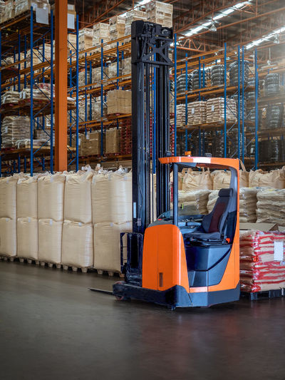 Reach trucks for perfect load control, material handling happens smooth and precisely in large warehouse. Racking  Built Structure Cardboard Box Distribution Warehouse Factory Forklift Freight Transportation Handling Indoors  Industry Jumbo Bag Manufacturing Equipment No People Pallet Pick Up Reach Trucks\ Safety Shelf Shipping  Shop Stack Storage Compartment Storage Room Transportation Warehouse