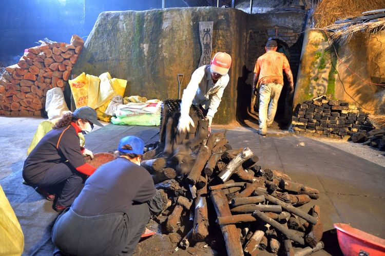 Making kiln-fired charcoal is a traditional handicraft industry. Charcoal Kilns In The Dark Hot Industry Toilet Tradition Black Burn Wood Charcoal Day Economic Give Kiln Labor Force Men Outdoors People Real People Work Hard Working