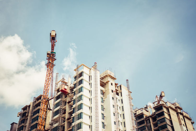 Low Angle View Of Crane By Buildings Against Sky