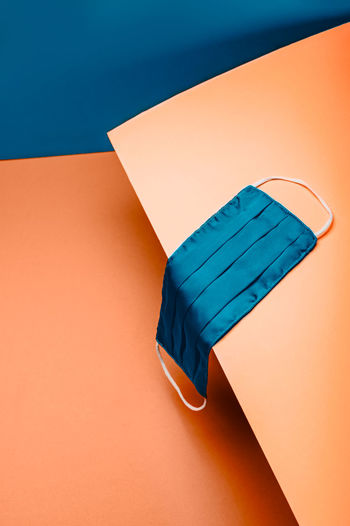 New normal with reusable protective silk face mask on blue and orange background, . trendy setting