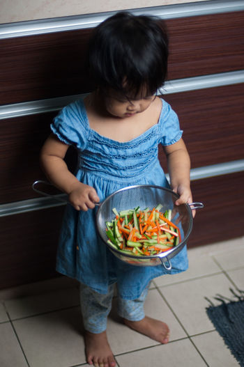 High Angle View Of Girl Holding Container With Carrot And Zucchini In Kitchen At Home