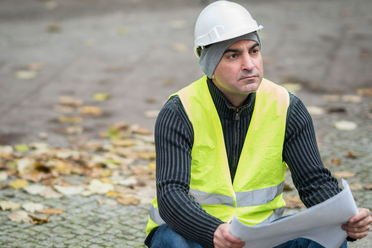 Thoughtful Engineer In Reflective Clothing Sitting On Road