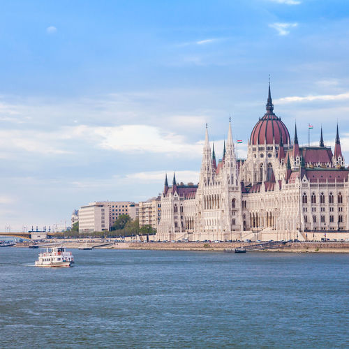Low Angle View Of Hungarian Parliament Building By River Against Sky