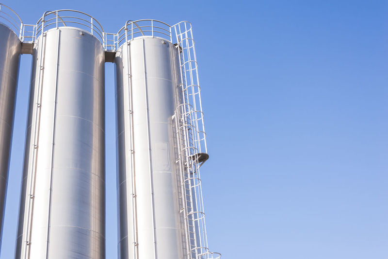 Low angle view of storage tanks against clear sky