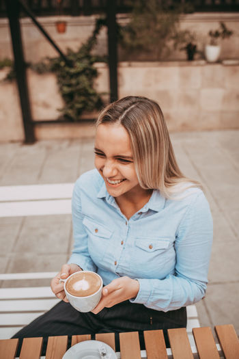 Young woman drinking coffee cup on table