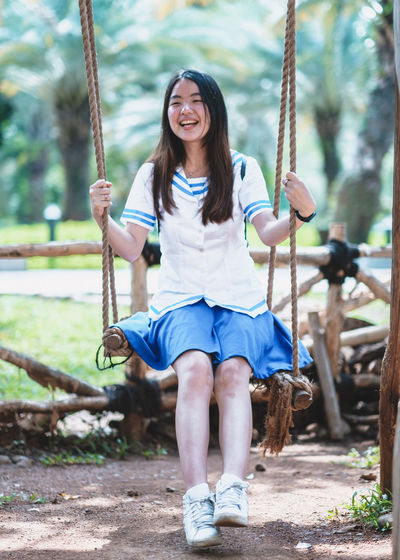 One Person Casual Clothing Swing Sitting Front View Smiling Playground Full Length Happiness Leisure Activity Looking At Camera Real People Portrait Emotion Lifestyles Long Hair Day Hairstyle Young Adult Hair Rope Swing Outdoors Outdoor Play Equipment Innocence