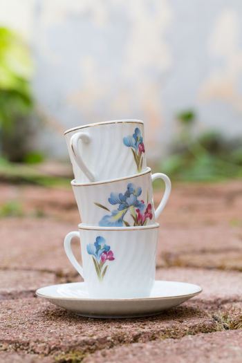 Stacked tea cups in the garden Tea Cups Afternoon Tea Antique Ceramics Close-up Crockery Cup Cups Day Drink Floral Pattern Focus On Foreground Food And Drink Mug Nature No People Outdoors Pattern Pitcher - Jug Porcelain  Refreshment Saucer Still Life Table Tea Cup