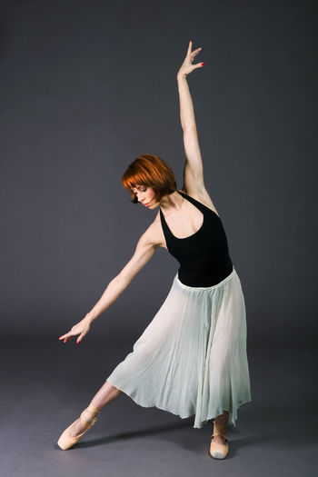Ballerina in ballet pose against gray background. Ballerina Woman Adult Balance Ballet Ballet Dancer Caucasian Dancer Dancing Elégance Full Length Girl Grace Grey Background Passion People Performance Performing Arts Pose Practicing Skirt Studio Shot Women Young Adult Young Women