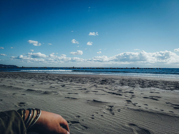 Midsection of man on beach against sky
