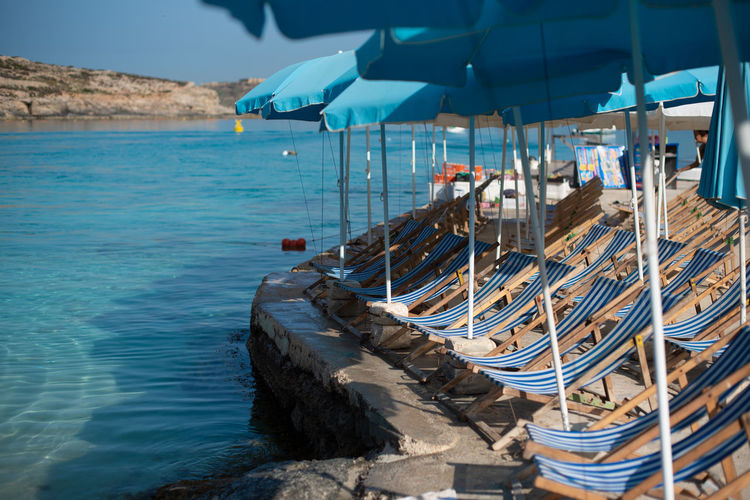 Deck chairs on rocks by sea against blue sky