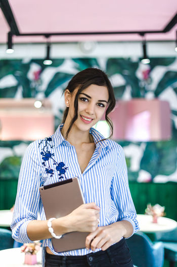 Portrait of smiling businesswoman with digital tablet standing in cafe
