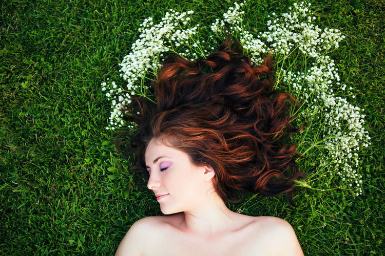 Directly above shot of young woman with long hair lying down on grass